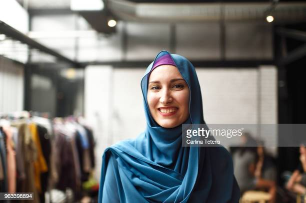portrait of a muslim woman in a clothing store - hijab - fotografias e filmes do acervo
