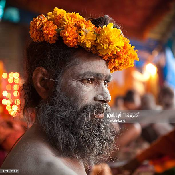 CONTENT] Portrait of a Naga sadhu holy man of Hinduism wearing marigold flowers on his head prepared for the big sacred bath Baisakhi Pramukh Shahi...