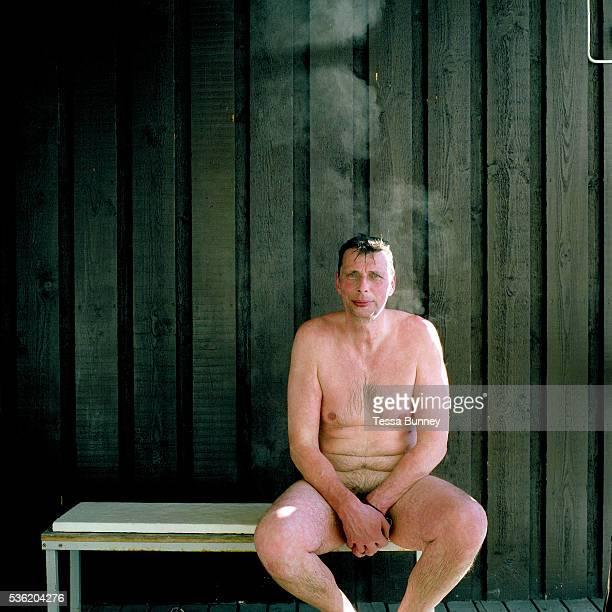 Portrait of a naked man sitting outside Vuorilammen sauna before ice swimming at the small lake of Vuorilampi Jyvaskyla Central Finland Ice swimming...
