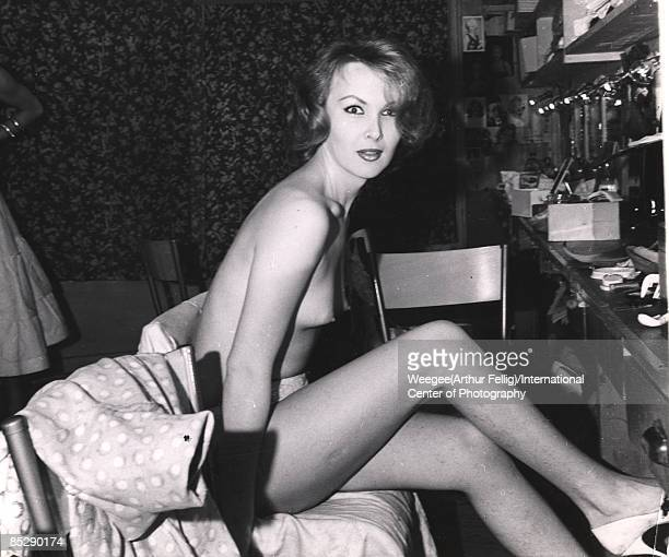 Portrait of a naked showgirl sitting in front of her makeup table while backstage at her dressing room ca 1950s Photo by Weegee/International Center...