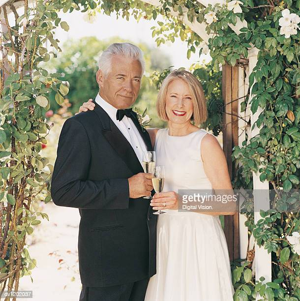 Portrait of a Newlywed Bride and Groom Holding Flutes of Champagne