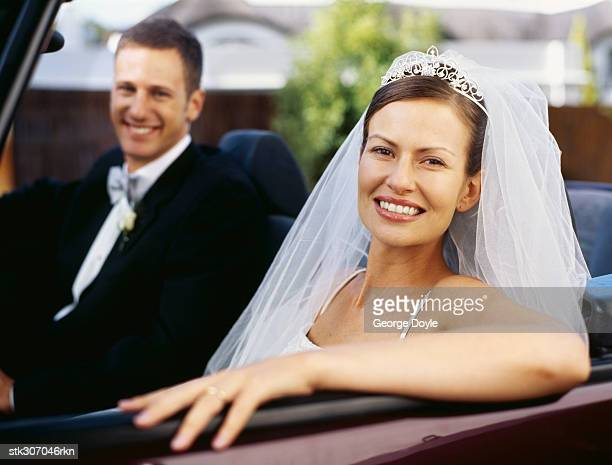 portrait of a newlywed couple sitting in a car