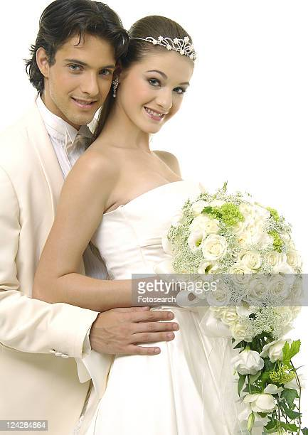 Portrait of a newlywed couple smiling and holding a bouquet of flowers