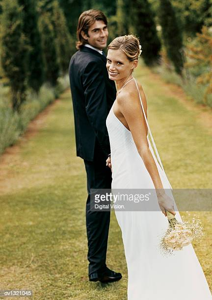 Portrait of a Newlywed Couple Standing on the Lawn of a formal Garden