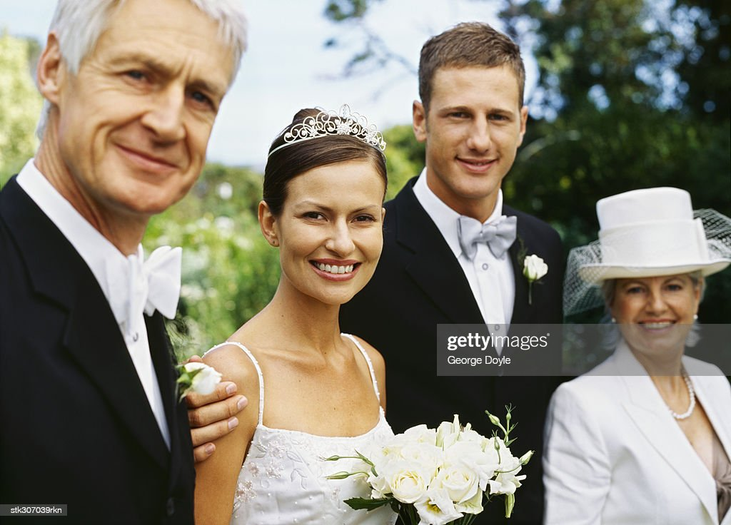 portrait of a newlywed couple standing with their parents : Stock Photo