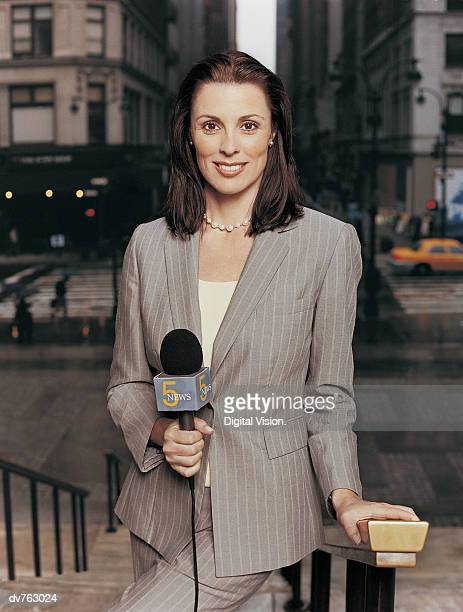 Portrait of a News Reporter Standing on Steps in the City and Holding a Microphone