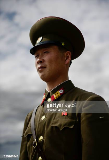 portrait of a north korean soldier, at the joint security area (jsa) seen from the north korean side of the military demarcation line (mdl) at panmunjom. the demilitarized zone (dmz) is the border between north and south korea - military demarcation line korea stock pictures, royalty-free photos & images