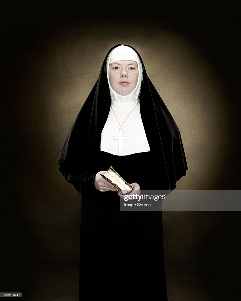 Portrait of a nun holding a bible : Stock Photo