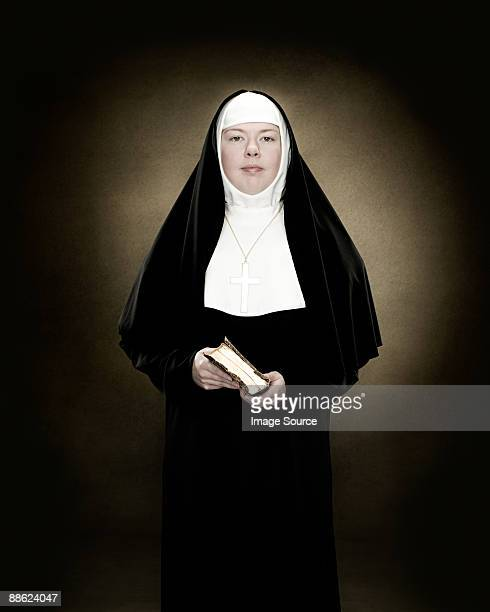 portrait of a nun holding a bible - bonne soeur photos et images de collection