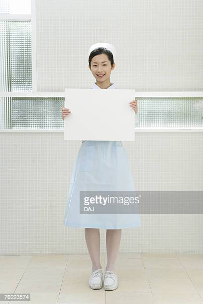 Portrait of a nurse holding a blank board, smiling and looking at camera, front view