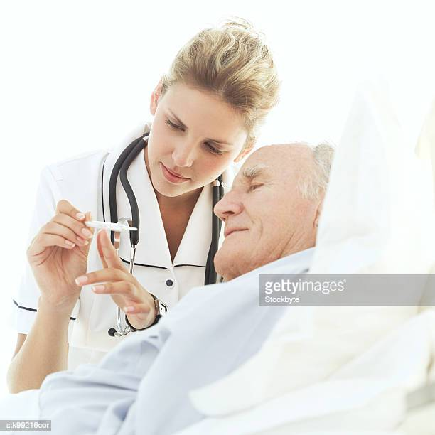 portrait of a nurse showing a thermometer to an elderly patient