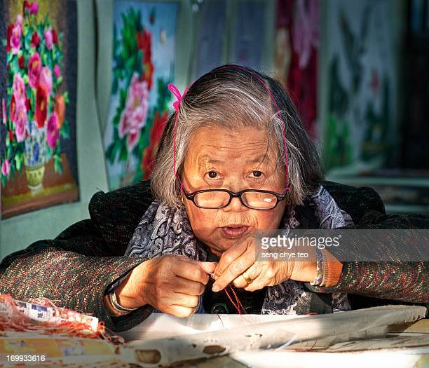 Portrait of a old master lady using needle sewing traditional art painting of flowers n scenery in china part of shanghai ,a historical old water...