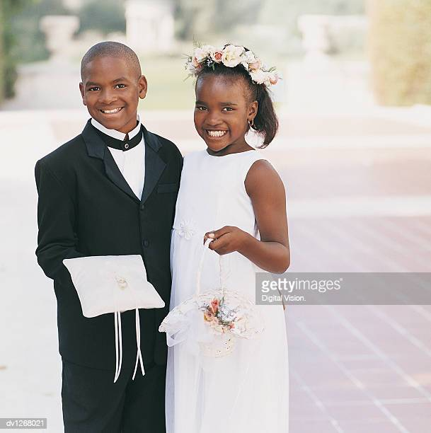 portrait of a page boy with his arm around a bridesmaid at a wedding - pageboy stock pictures, royalty-free photos & images
