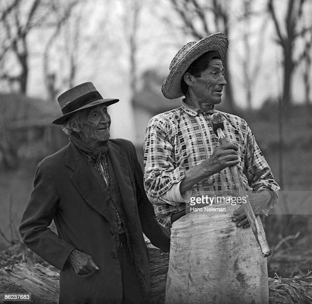 Portrait of a pair of elderly men, on in a jacket and fedora and fhen other, somewhat younger, in an apron, straw hat and carrying a hammer, Fundo La...