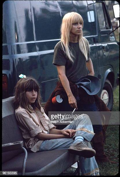 Portrait of a pair of festival goers one a boy seated on a car bench and the other a woman photographer who stands and smokes as they watch the...