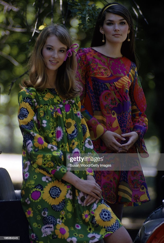 Portrait of a pair of models, one in a green floral print dress and the other in a red paisley print dress, as they pose on a carriage in Central Park, New York, New York, August 1966. The photo was taken as part of a fashion shoot for Glamour Magazine.