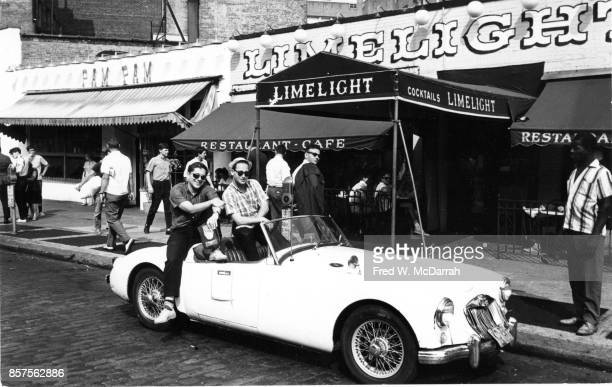Portrait of a pair of unidentified men as they sit on an MG MGA twoseat convertible in front of the Limelight Coffee House to watch the seventh...