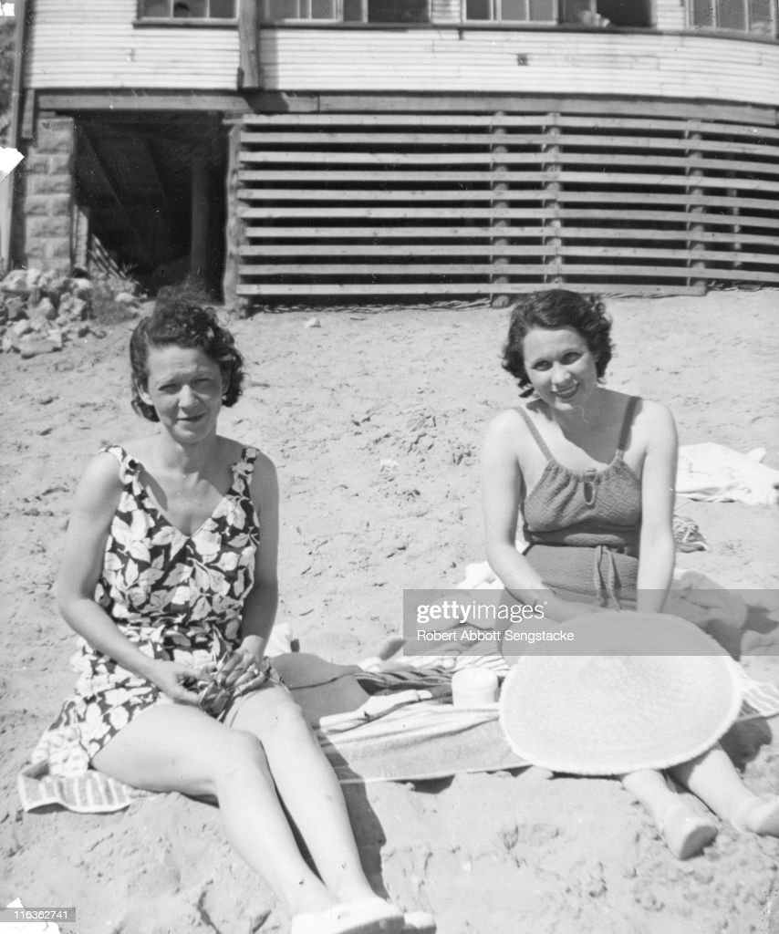 Portrait of a pair of unidentified women (friends and/or family members of future newspaper publisher John H. Sengstacke) as they sit on the beach outside the Idlewild Club House, Idlewild, Michigan, September 1938. Idlewild, known as 'the Black Eden,' was a resort community that catered to African Americans, who were excluded from other resorts prior to the passage of the Civil RIghts Act of 1964.