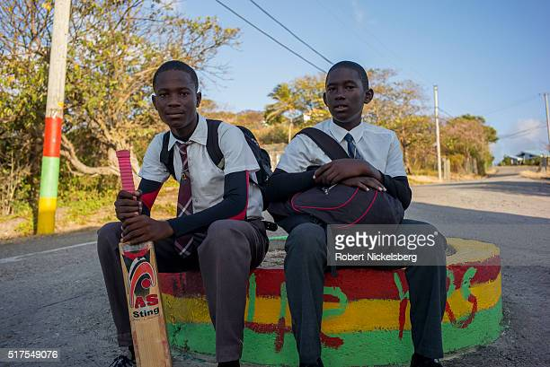 Portrait of a pair of uniformed schoolboys, one with a cricket bat, as they wait for a local transport van, Carriacou island, Grenada, March 4, 2016.