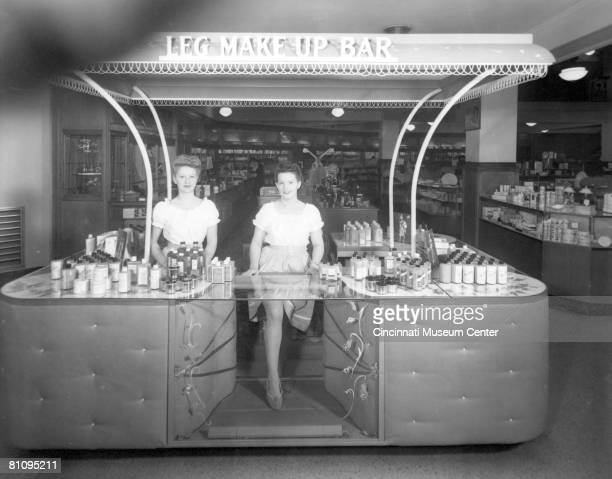 Portrait of a pair of women at the service counter of an unidentified department stores' 'Leg MakeUp Bar' Cincinnati Ohio 1940s Due to the wartime...