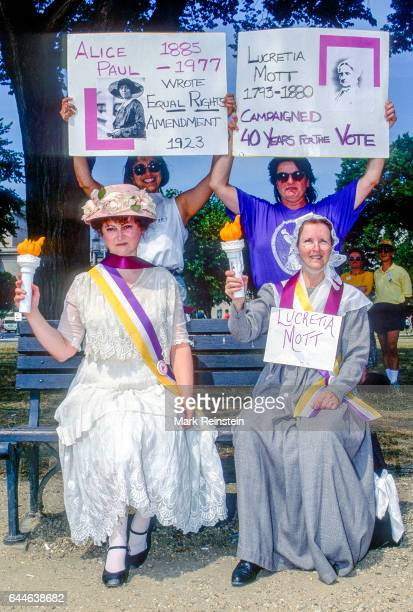 Portrait of a pair women one dressed as suffragist Alice Paul and one as Lucretia Mott who hold torches as they sit on a bench during a rally in...