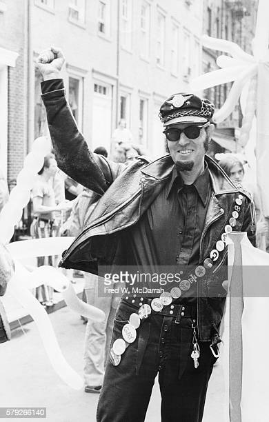 Portrait of a paradegoer dressed in a leather jacket crossed with a strap that displays various gay rights pins as he poses during the Sixth Annual...
