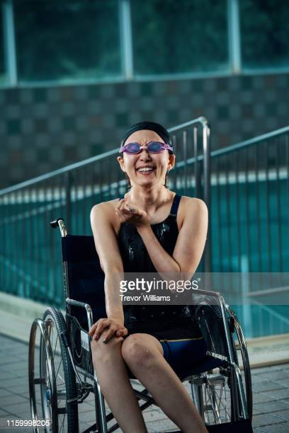 portrait of a paraplegic woman in a wheelchair next to a pool after training for competitive swimming - paraplégico - fotografias e filmes do acervo