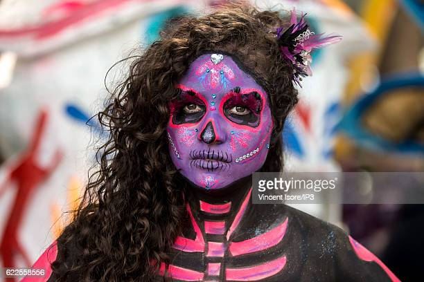 Portrait of a participant who wears a colorful costume and parades through the streets during the 'Catrinas Parade' a joyful annual event celebrated...