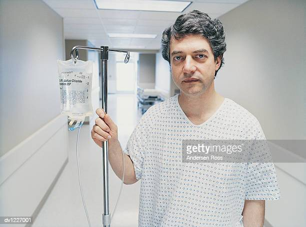 portrait of a patient standing in a hospital corridor - hospital gown stock pictures, royalty-free photos & images