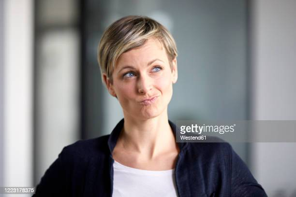 portrait of a pensive businesswoman in office - puckering stock pictures, royalty-free photos & images