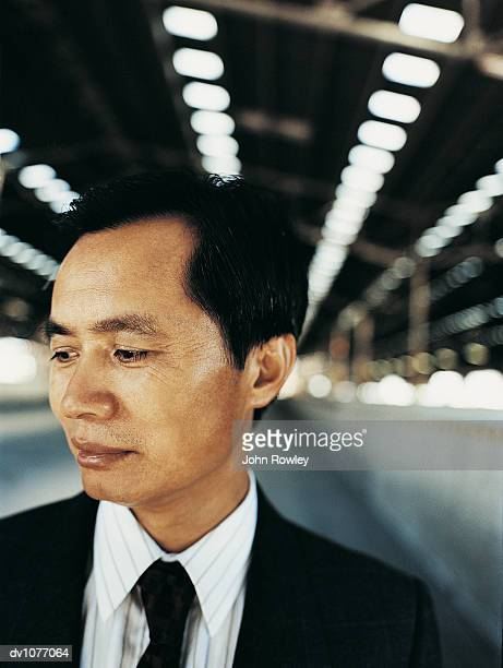Portrait of a Pensive Mature Businessman Looking Sideways and Standing in a Factory