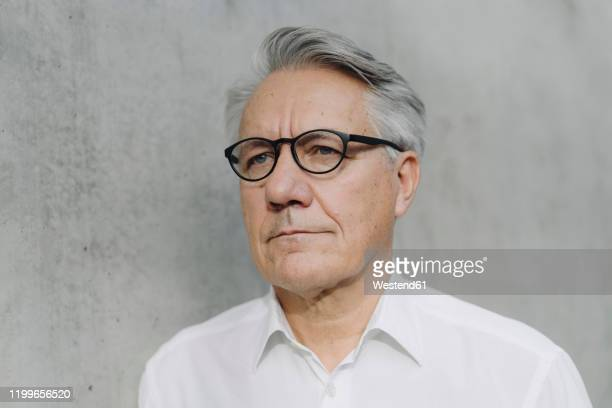 portrait of a pensive senior businessman at a concrete wall - looking away stock pictures, royalty-free photos & images