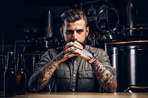 Portrait of a pensive tattooed hipster male with stylish beard and hair in the shirt in indie brewery. 1071778028