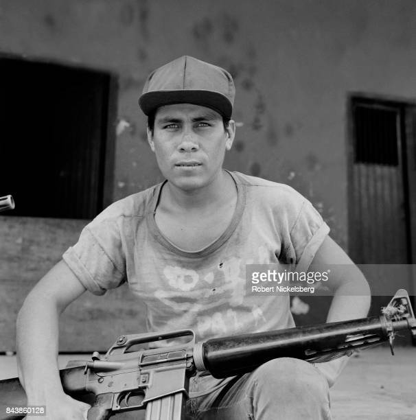 A portrait of a People's Liberation Forces guerrilla fighter as he sits in front of a building occupied during an attack in Cinquera El Salvador May...