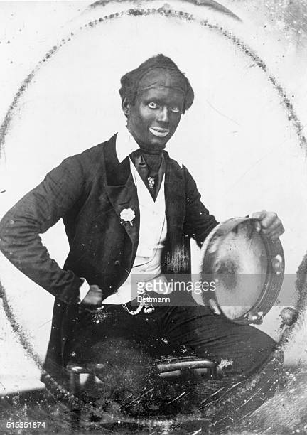 Portrait of a performer in wig and blackface. He is shown seated, holding a tambourine. Undated photograph, circa 1900.