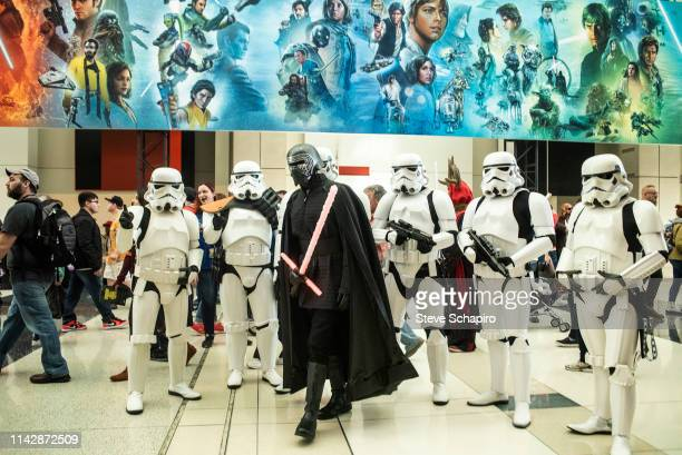 Portrait of a person dressed as 'Kylo Ren' in front of others dressed as 'Stormtroopers' at the Star Wars Celebration event at Wintrust Arena,...