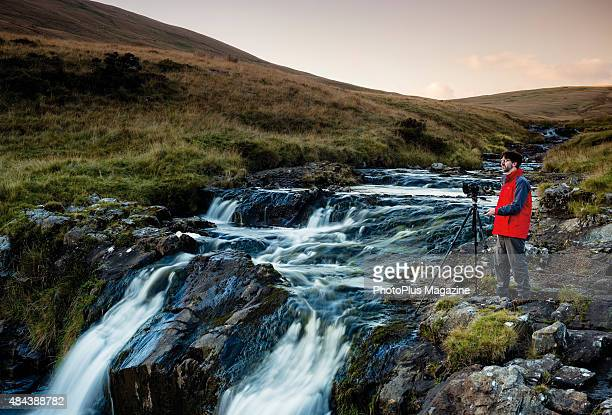 Portrait of a photographer with a tripodmounted DSLR camera taking pictures of a river in the hills north of the Dulais Valley in Wales taken on...