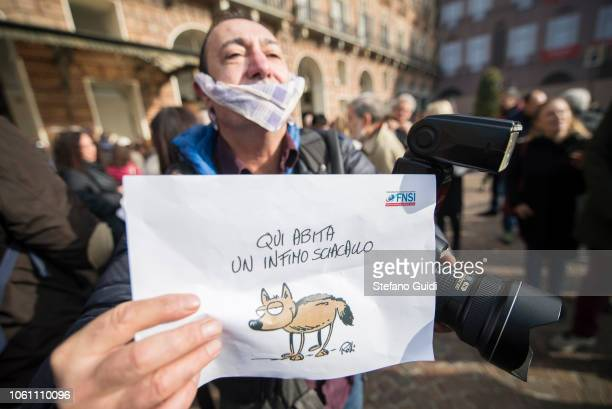 Portrait of a photojournalist with a gag and holding in his left hand a protest sign with the words 'Here lives a poor jackal' and in the left the...