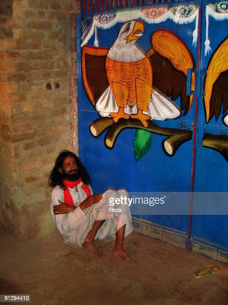 Portrait of a pilgrim immersed in his pray at the enterance of a shrine of one of Lal Shahbaz Qalandar's disciple a 13th century Sufi Master...