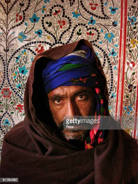 portrait of a pilgrim in front of Sindh kashi tiles and mirror works inside the shrine of Bodla Bahar one of the main disciple of Lal Shahbaz...