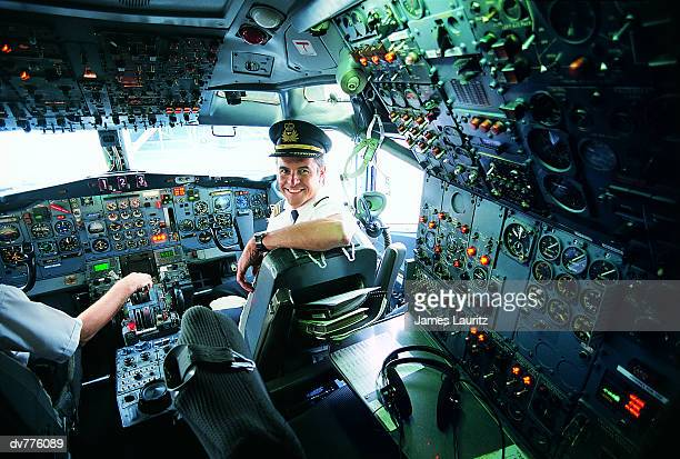 portrait of a pilot sitting at the controls of a commercial aeroplane - cockpit stock pictures, royalty-free photos & images