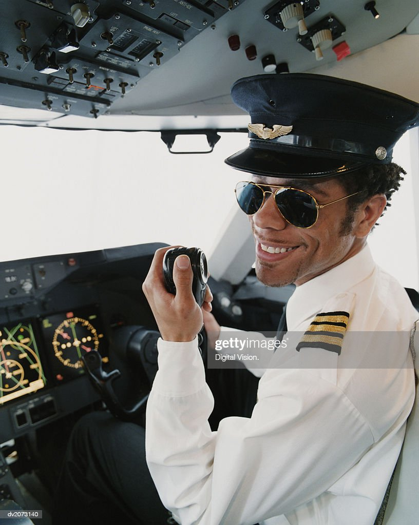 Portrait of a Pilot Sitting in the Cockpit, Holding a Radio : Stock Photo