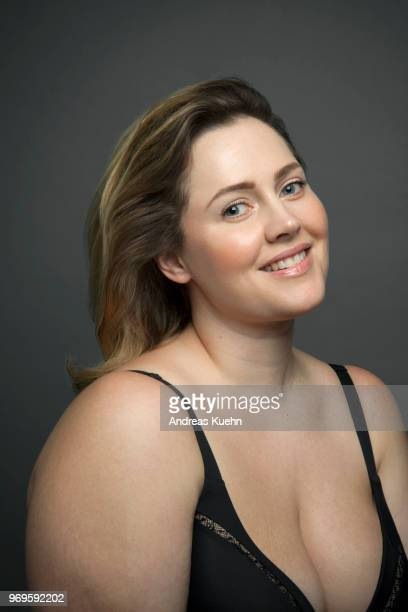 Portrait of a plus size woman in her late thirties with a smile wearing a black bra and showing some cleavage.