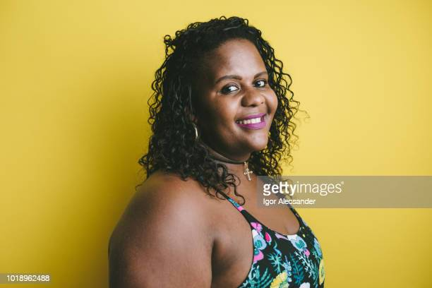 portrait of a plus size woman on a yellow background - voluptuous black women stock photos and pictures