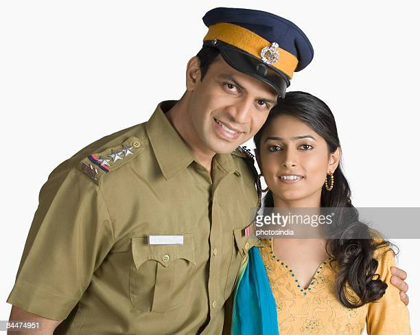 Portrait of a police officer standing with his arm around his wife