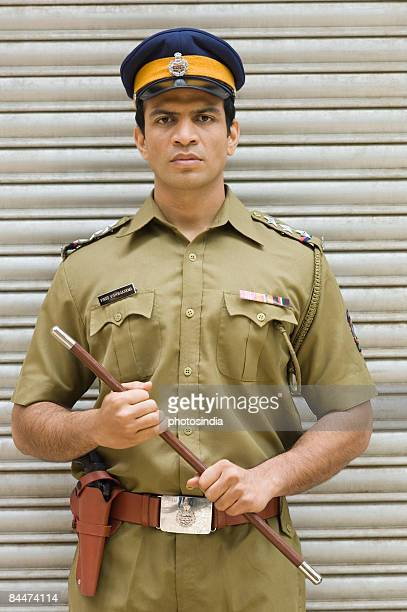 Portrait of a policeman holding a nightstick