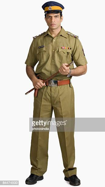 portrait of a policeman holding a nightstick - uniform cap stock pictures, royalty-free photos & images