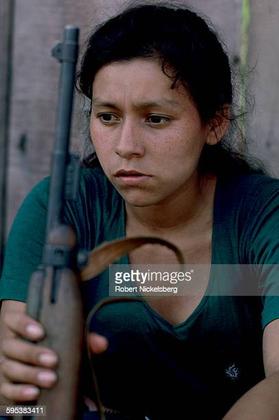 Portrait of a Popular Revolutionary Forces guerrilla as she sits against a wall a rifle in her hands Corinto El Salvador February 1 1983 At the time...