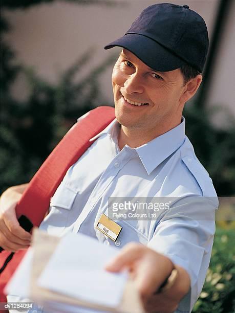 portrait of a postman delivering mail - carteiro imagens e fotografias de stock