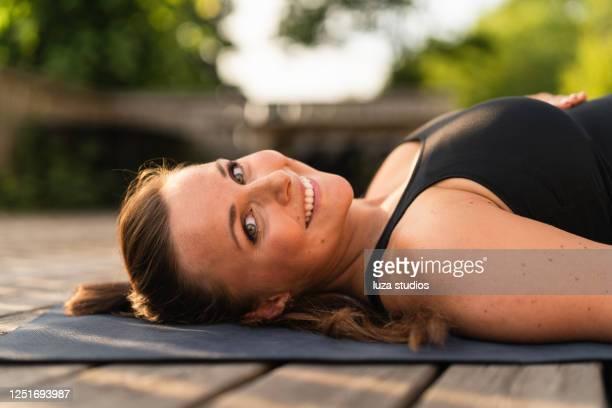 porträt einer schwangeren frau, die sich auf ihrer yogamatte hinlegt - lying down stock-fotos und bilder